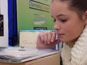 A school pupil watching a rare-earth magnet levitated over a sample of bulk superconductor
